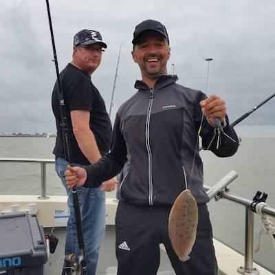 man met vissen welke gevangen zijn tijdens tongvissen westerschelde