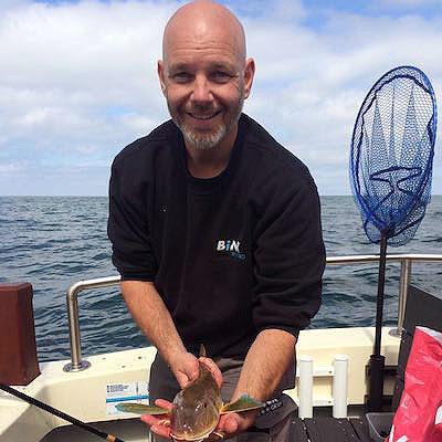 Man laat zien welke haai hij heeft gevangen tijdens de dag haaienvissen op de Noordzee
