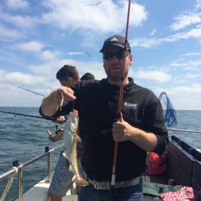 man toont vangst na dagje zeevissen zeeland